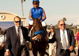 Co-owners Joe Torre, left, and Bernie Schiappa, right, escort favored Game On Dude and Martin Garcia into the winner's circle after victory in the Grade I $1,000,000 Pacific Classic Sunday,  at the Del Mar Thoroughbred Club. BENOIT PHOTO